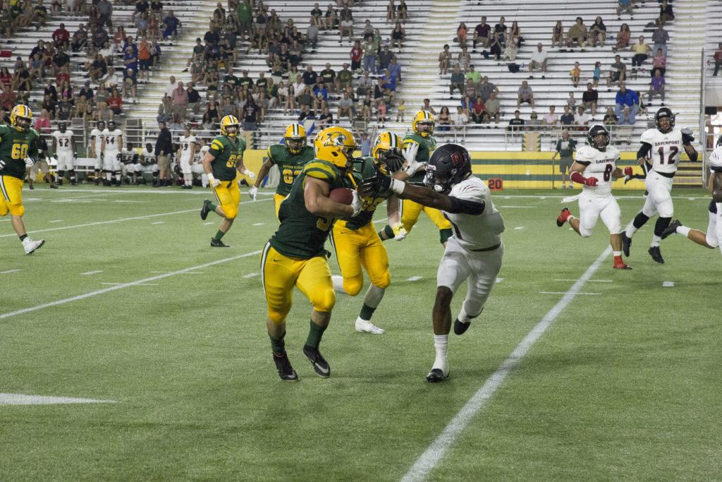 Photo by Neil Flavin: Junior running back Jake Mayon caps-off the first quarter of the Wildcats game against Davenport.