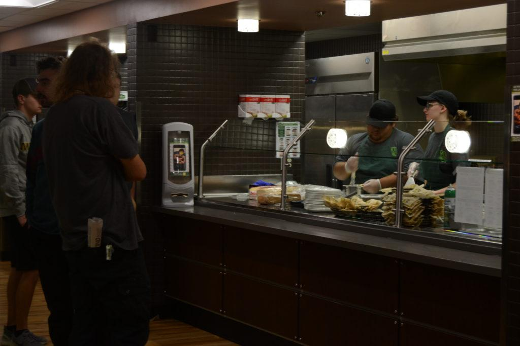 Photo by Lindsey Eaton: Servers at the Wildcat Den prepare food for a line of NMU students. The Den is one primary location to find new food products from Reinhart.