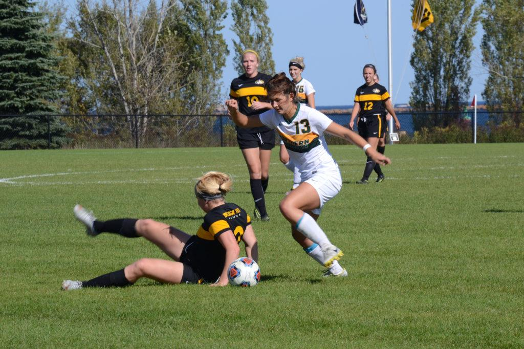 Photo by Lindsey Eaton: Junior defender Sophia Sachs dribbles around a Michigan Tech player, who is sitting down for whatever reason. Sachs appeared and started in 17 games last season and was named Newcomer of the Year the previous season.