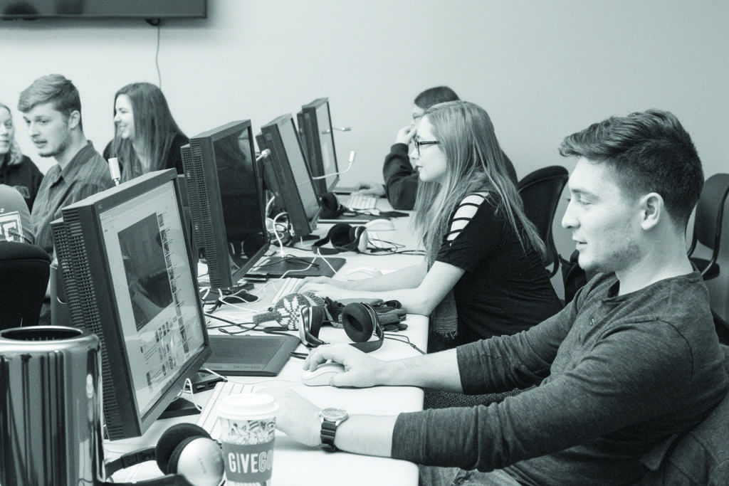 Photo by Kat Torreano: NMU students in the 4Reels club work on editing movies that they have filmed during their weekly meeting at 7:30 p.m. on Monday in room 75 in the Art and Design Building. On the right is club president Jack Cole.