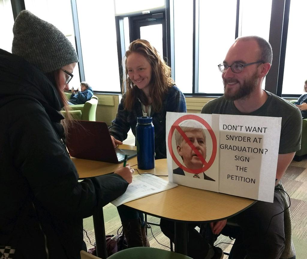 Photo by Winter Keefer: Students Laura Long and Nathan Frischkorn collect student signatures in opposition of Gov. Rick Snyder speaking at May commencement.