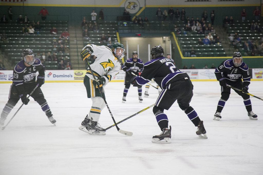 Photo+by+Neil+Flavin%3A+Junior+forward+Troy+Loggins+takes+the+puck+and+tries+to+manuever+around+some+Minnesota+State+players+on+his+way+to+goal.+Along+with+senior+forward+Robbie+Payne%2C+Loggins+is+ranked+among+the+top+scorers+in+the+WCHA.