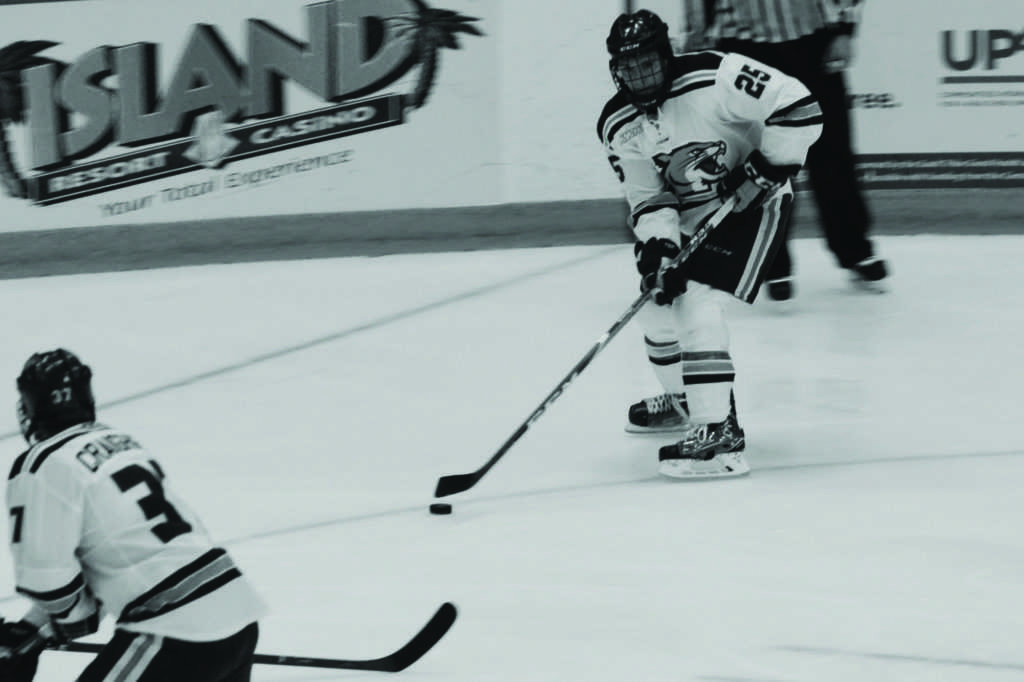 Photo+by+Lindsey+Eaton%3A+Freshman+forward+Caleb+Schroer+skates+down+the+rink+with+the+puck+in+a+game+earlier+in+the+season.+Sophomore+forward+Darien+Craighead+cruises+down+the+ice+as+a+potential+pass+option.