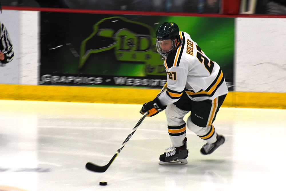 Photo by Lindsey Eaton: Freshman defender Adam Roeder skates down the ice and surveys the area for a fellow Wildcat to pass to. Prior to NMU, Roeder played for the Janesville Jets where he was captain.