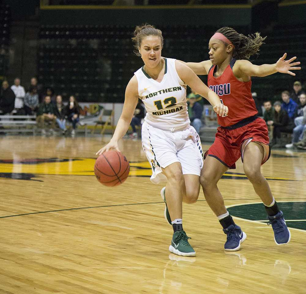 Photo by Neil Flavin: Junior guard Sydney Dillinger attempts to drive past a Saginaw Valley State player. Last season, Dillinger start- ed 11 of her 29 games played, accumulating 731 minutes.