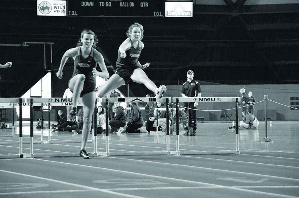 Michelle Juergen and Ine Mylle compete in hurdles Saturday at Marrquette Superior Dome.  Photo by: Lindsey Eaton