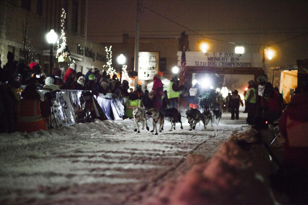 Sled dog teams bolt from the start as crowds cheered them on at last years UP 200 on Washington Street.
