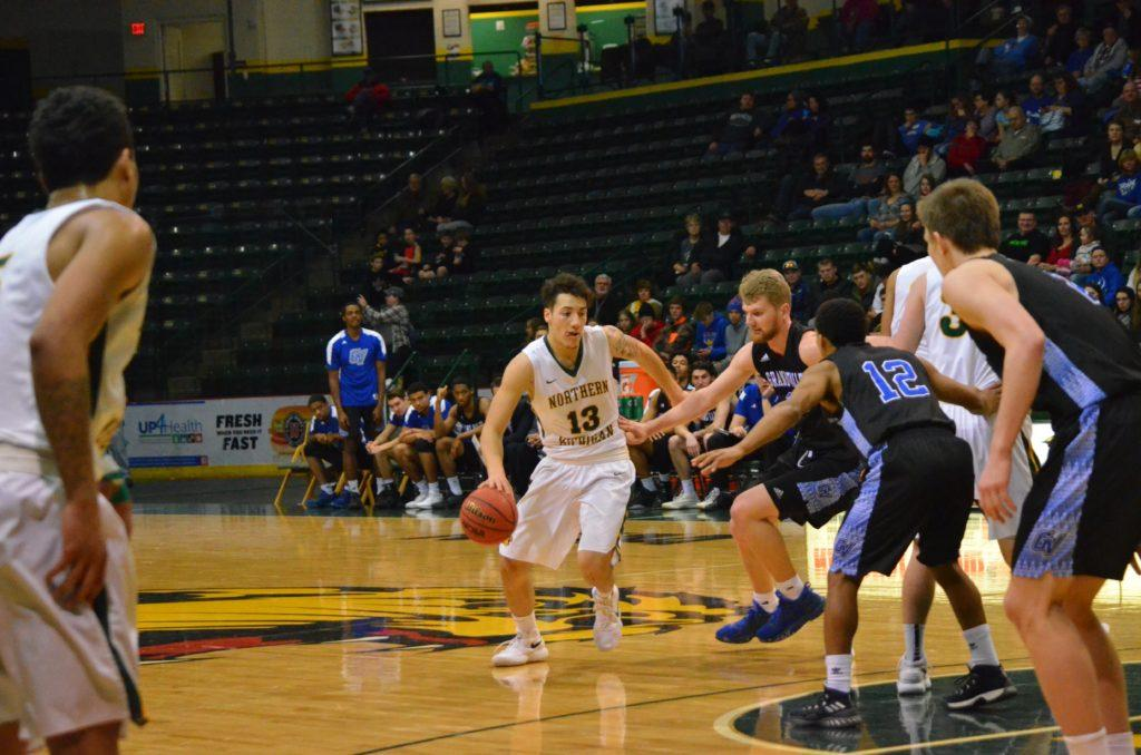 Junior guard/forward Isaiah Johnson dribbles around a trio of GVSU defenders Saturday at the Berry Events Center. Photo by Emma Case