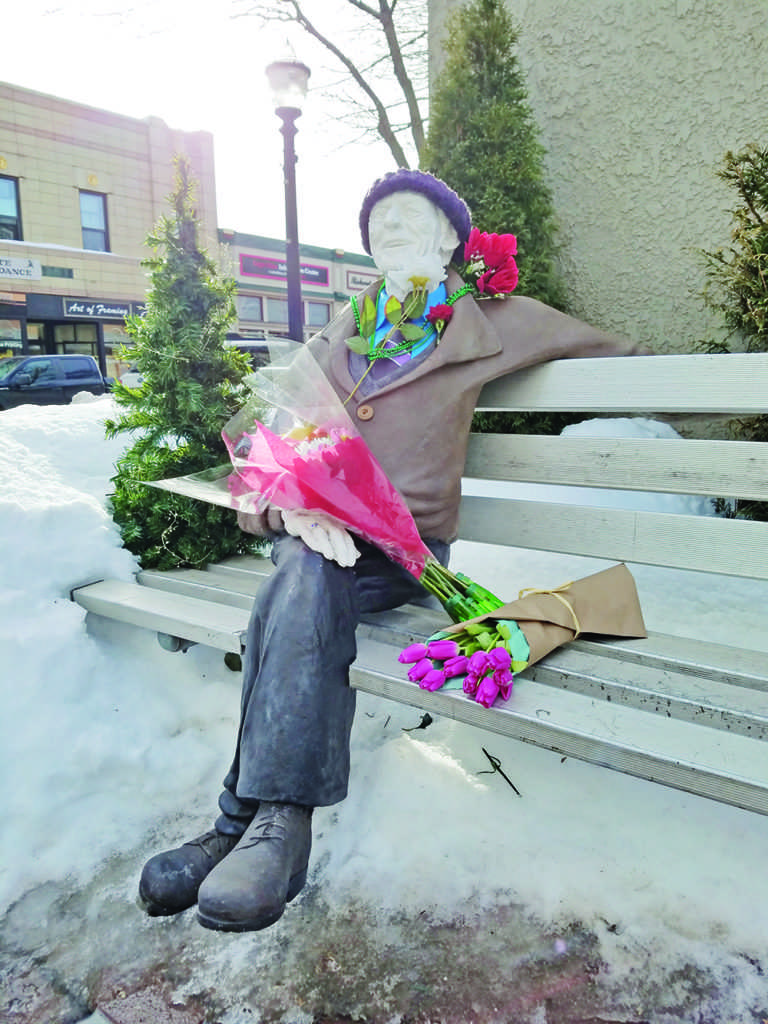 Community members have decorated the statue of Phil Niemisto located in his pocket park.