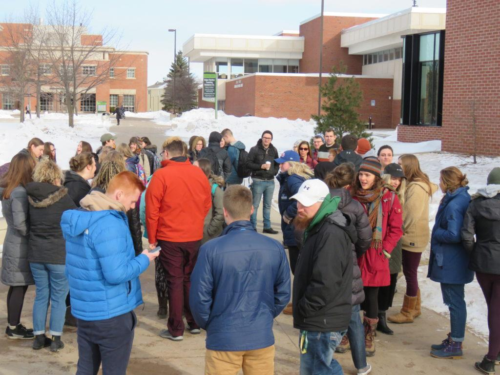Over 50 NMU students, faculty and administration gather in the academic mall to stand in solidarity with those from the Florida high school that experienced a mass shooting a month ago where 17 people died. Photo by: Trevor Drew