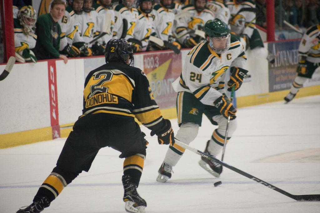 Senior forward Zach Diamantoni skates the puck into the offensive zone as he's guarded by Michigan Tech freshman defender Seamus Donohue and his teammates eagerly look on. Dia- mantoni skated in 143 games in his four years at NMU, scoring 16 goals and tallying 43 assists, and currently has the sixth most points for the Wildcats this season with 19. Photo by: Lindsey Eaton