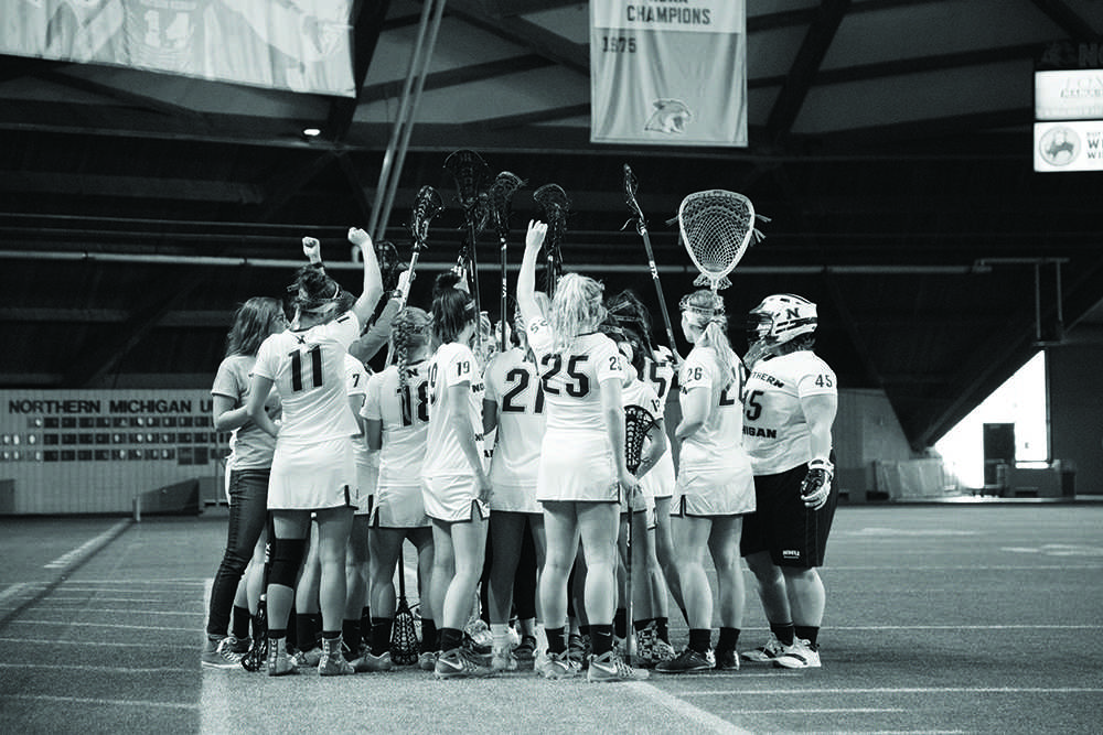 Freshmen+midfielders+Bianca+Kinder+and+Hannah+Seaman%2C+sophomore+midfielder%2Fdefender+Leiss+Luyckx+and+senior+goaltender+Brianna+Bangle+stand+in+the+foreground+of+a+team+huddle+Wednesday+against+St.+Paul.+%0APhoto+by%3A+Emma+Case