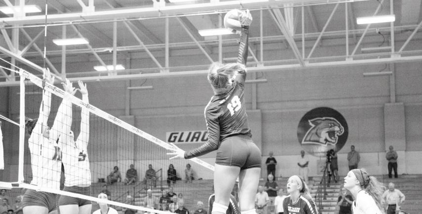 Senior outside hitter Autumn Monsma spikes the ball while her opponents set up a block during last season. Photo by: Neil Flavin