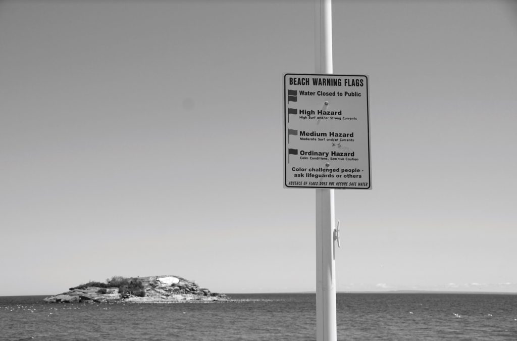 A sign depicting each of the beach warning flags along with their significance is displayed near Picnic Rocks off of Lakeshore Drive. Lifeguards recommend swimming in the lake only when the green flag is posted. Photo by: Kat Torreano