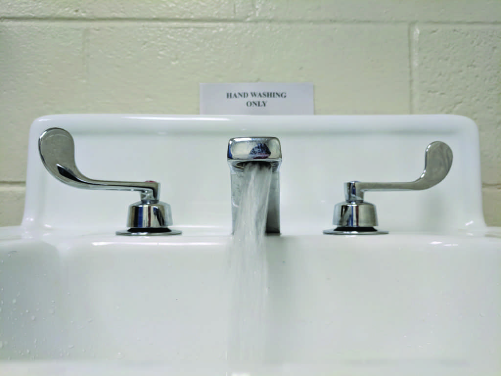 A sign designates a sink in a Thomas Fine Arts bathroom to just hand washing. Sinks and water fountains in this facility, the PEIF and the Learning Resource Center were found to have high levels of lead after multiple rounds of testing were conducted by university officials and consultative groups.  Photo by Tim Eggert