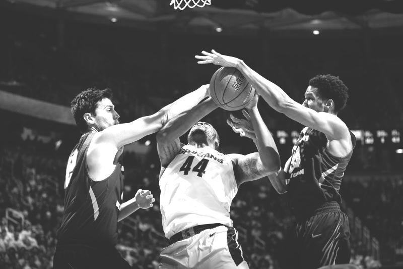 Senior center Max Pendergast (left) and junior center Myles Howard (right) defend against MSU standout center Nick Ward. The Wildcats struggled to find a shooting stroke and lost to the No. 10 ranked Spartans. Photo courtesy of NMU Athletics