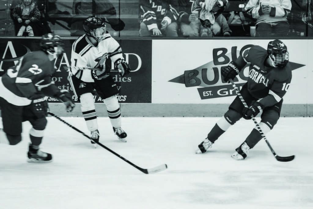 Senior Wildcat defenseman Tony Bretzman sends the puck up the ice past two Cornell forwards. Photo by Jacob Darner