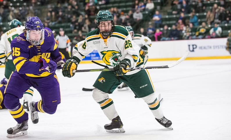 Freshman forward Ty Readman chases down a puck while trying to hold back a Minnesota State Maverick.  Photo courtesy of NMU Athletics