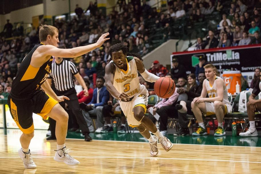 Junior guard Sam Taylor drives the lane against a Michigan Tech University defender in a 63-59 win. Photo courtesy of NMU Athletics