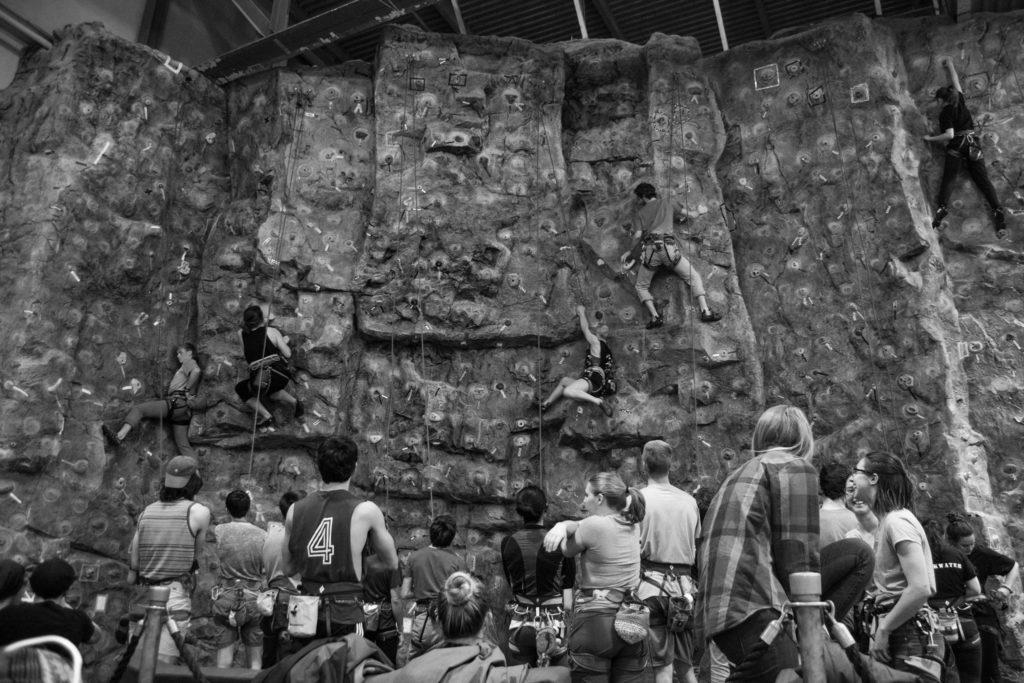 Students and community members gather around the indoor rock wall at the PEIF for the Coffee and Climb event.