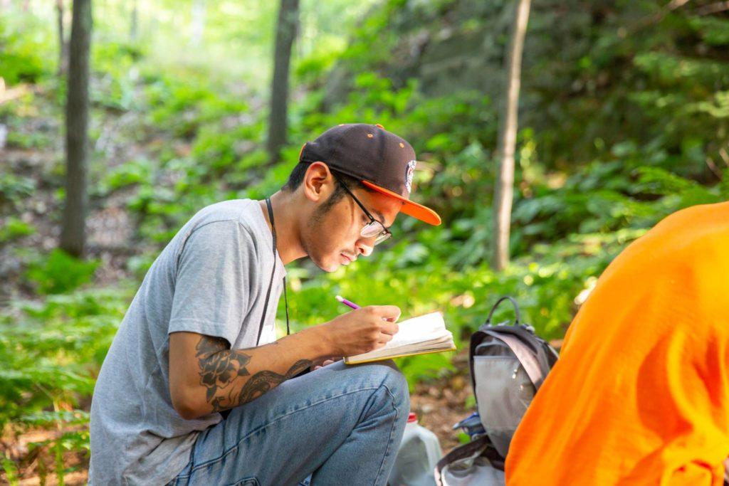 """Guiancarlo """"Carlo"""" Estupigan sketches in a notebook. The 25-year-old sophomore fish and wildlife management major was found dead Sunday near the Yellow Dog River after missing for three days.   Photo courtesy of NMU Marketing and Communications Office."""