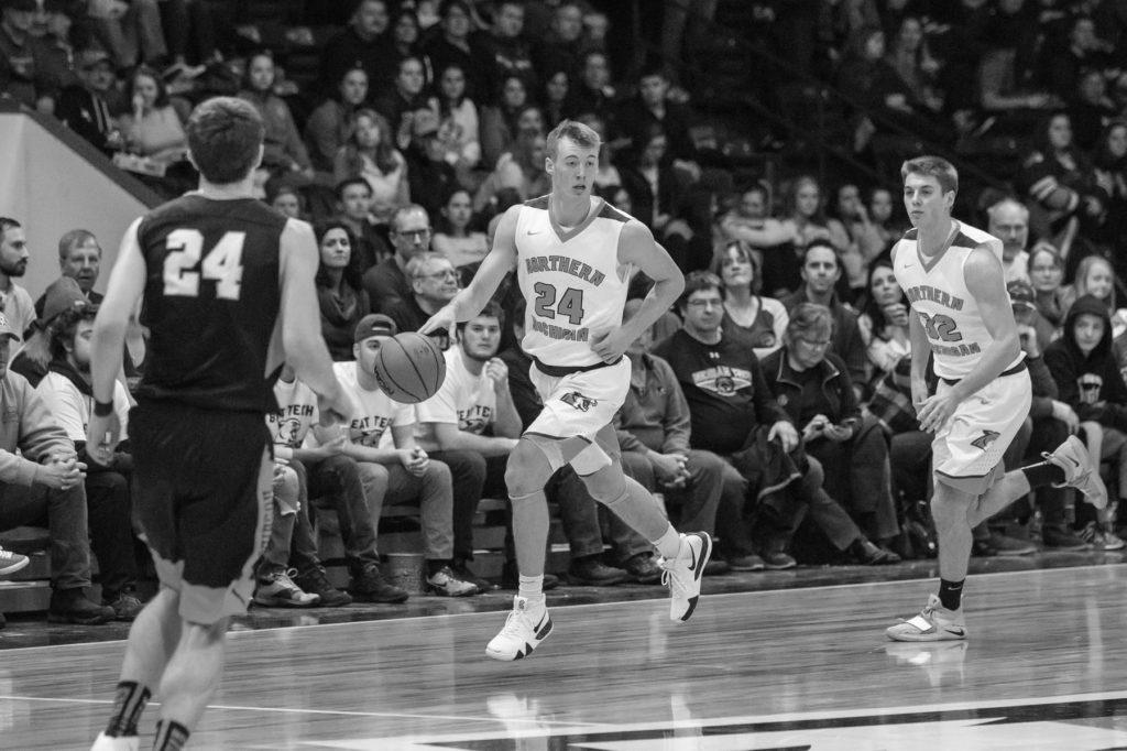 In an earlier season matchup against Michigan Tech University, sophomore guard Alec Fruin looks to make a play while junior guard Marcus Matelski trails behind. Photo courtesy of NMU Athletics