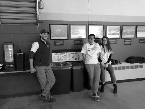 Volunteer Dylan Gonda—a recent NMU graduate—and perspective EcoRep and environmental science major Andrew Jessen sit with elementary major and EcoRep Maggie Pung at a sorting station at the Zero-Waste Challenge hockey game.