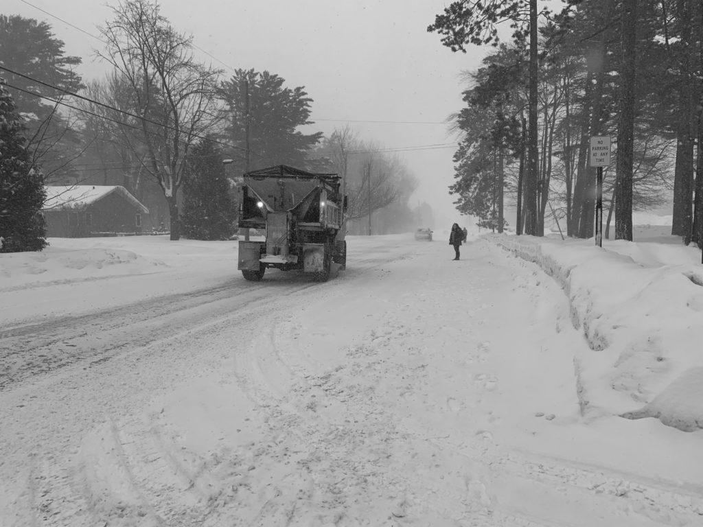 A student waits for a NMU plow truck to pass before crossing Center Street. The NMU Grounds Department has over 20 miles of sidewalks, 16 miles of road and 70 acres of parking lots and driveways to clear snow from.  Kelsii Kyto