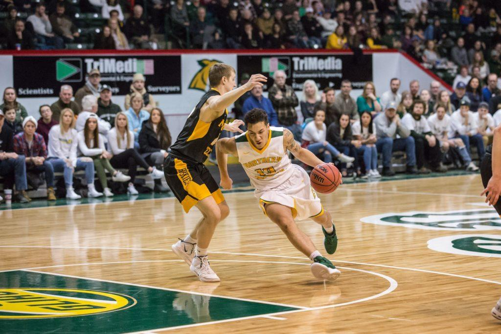 Senior guard/forward Isaiah Johnson drives down the lane aggressively in a matchup against Michigan Tech University earlier in the season.  Photo courtesy of NMU athletics
