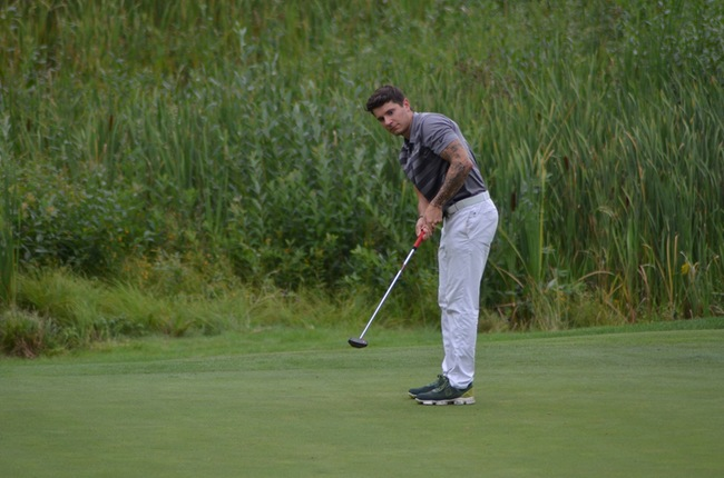 Senior+Austin+Elsner+eyes+down+a+putt+from+the+weeds.%0A%0APhoto+courtesy+of+NMU+athletics