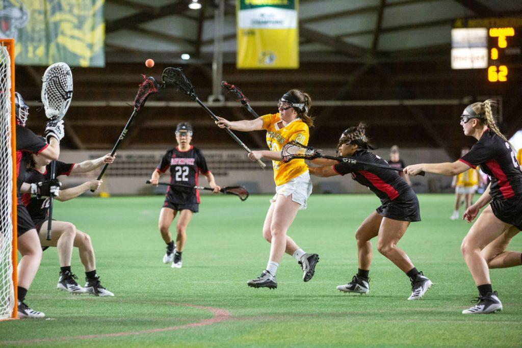 Demonstrating her natural ferocity, junior attacker Angelica Bogden knives through Davenport defenders in pursuit of lighting up the back of the net with relentless authority.  Photo courtesy of NMU athletics