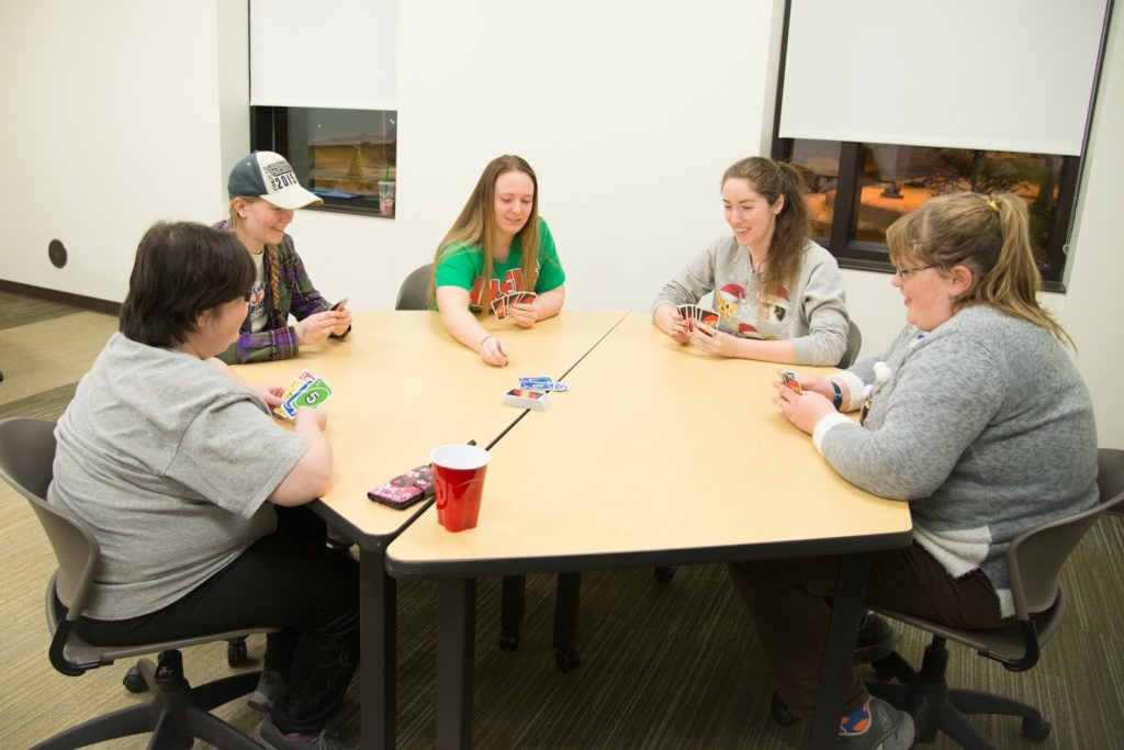 Members of NMU's Best Buddies sit around a table in Jamrich Hall playing the card game UNO during a  Valentine's Day celebrataion. Best Buddies is an active student organization with goals of spreading inclusion. Photo courtesy of Emma Goebel