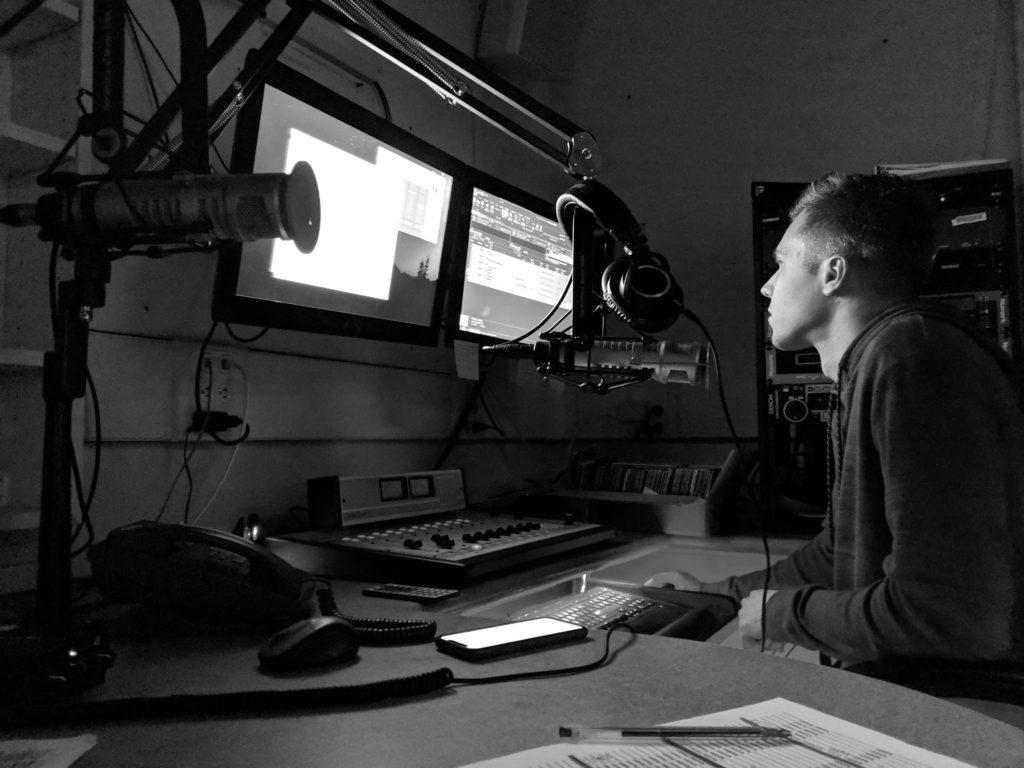 Photo+by+Tim+Eggert+%2F+Student+DJ+Cameron+Rhyman+plays+music+in+a+Radio+X+studio+booth.+