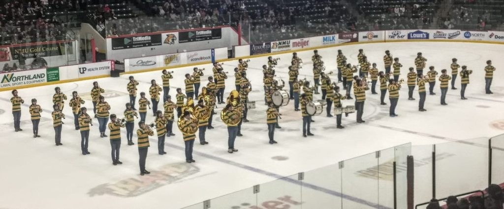 Photo courtesy of Richard Hamilton NMU's Marching Band stands on the ice of the Berry Events Center during a hockey game against Lake Superior State.  The marching band is using ASNMU-funded Cat Cleats. Photo courtesy of Richard Hamilton.