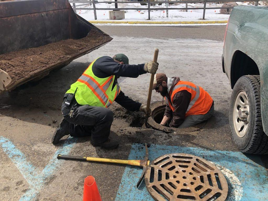 Jeff Skoog and Brad Gischia, members of the Grounds Department work on a deteriorating manhole near the handicap parking in Lot 36. To ensure safety, they are temporarily fixing the crack in cement before the foundation can be entirely replaced. Photo by Maggie Duly