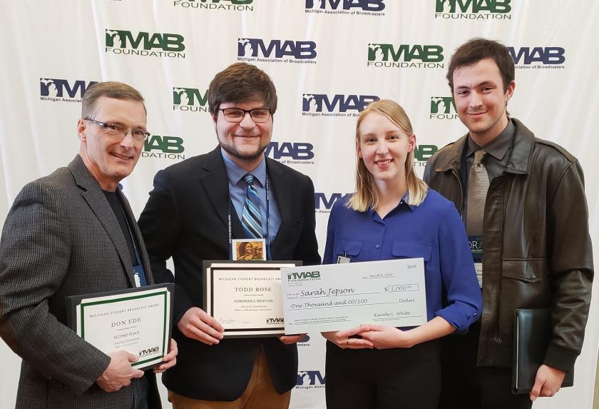 HISTORY OF GRANDEUR—Dwight Brady, Professor of Multimedia Journalism stands with student winners of broadcasting awards.