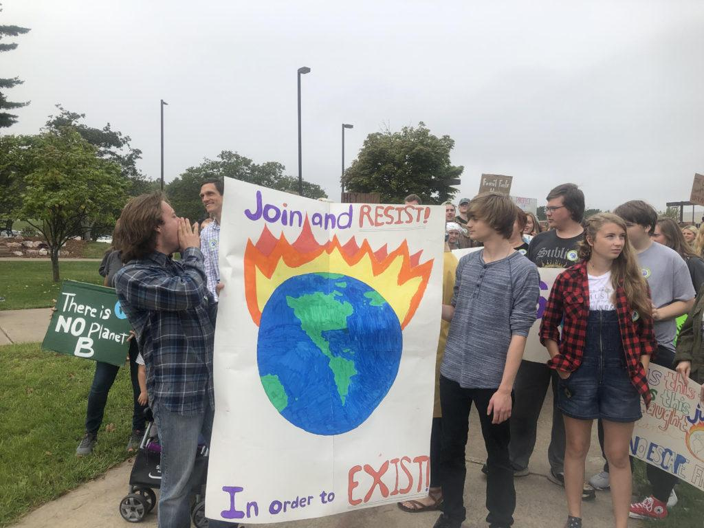 """PLANET, NOT PROFIT—Ishpeming High School seniors Kyle Erickson (left) and Tyler Larson (right) march for climate, chanting to implement the """"Green New Deal."""" The march took place on NMU campus Friday, Sept. 20, as part of a world-wide initiative to demand urgent action on climate change. A youthful presence led the cause across the globe.  Denali Drake/NW"""
