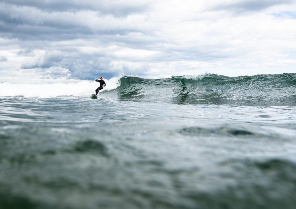"""CATCH A WAVE—Surfing in Lake Superior presents more challenges than ocean surfing, as lake waves are shorter lived and accompanied by a large amount of wind.  McCarty's Cove and """"The Zoo,"""" or Sunset Point at Presque Isle, create the ideal breeding ground for ridable waves. Photo courtesy of LIam Kaiser."""