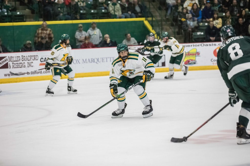 BRING+OUT+THE+BROOMS%E2%80%94NMU+forward+Andre+Ghantous+plays+defense+in+the+Wildcats%E2%80%99+season-opening+5-3+loss+to+Michigan+State+on+Friday%2C+Oct.+11.+The+Wildcats+are+on+a+three-game+winning+streak+after+sweeping+Ferris+State+University%2C+clawing+a+No.+20+national+spot+on+the+USCHO+poll.+The+Wildcats+now+have+their+sights+on+the+Alabama-Huntsville+Chargers.+Puck+drop+is+set+for+7+p.m.+on+Friday%2C+Nov.+1.+Photo+courtesy+of+NMU+Athletics