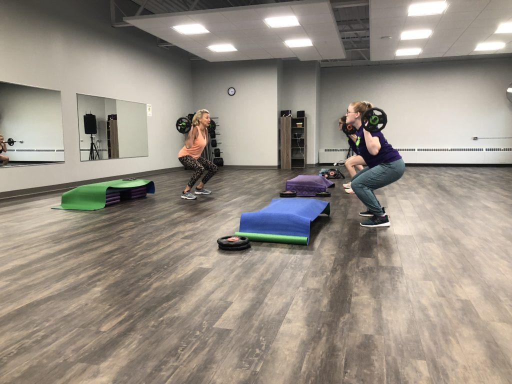 FEEL THE BURN—Instructing fitness classes for over 30 years, Lynne Mestnik has been at NMU for the past three years guiding students, like Caitlin Sternberg and Natalie Nesburg above, through Yoga Flow and Power 50 to build their strength and aid relaxation.  Maggie Duly/NW