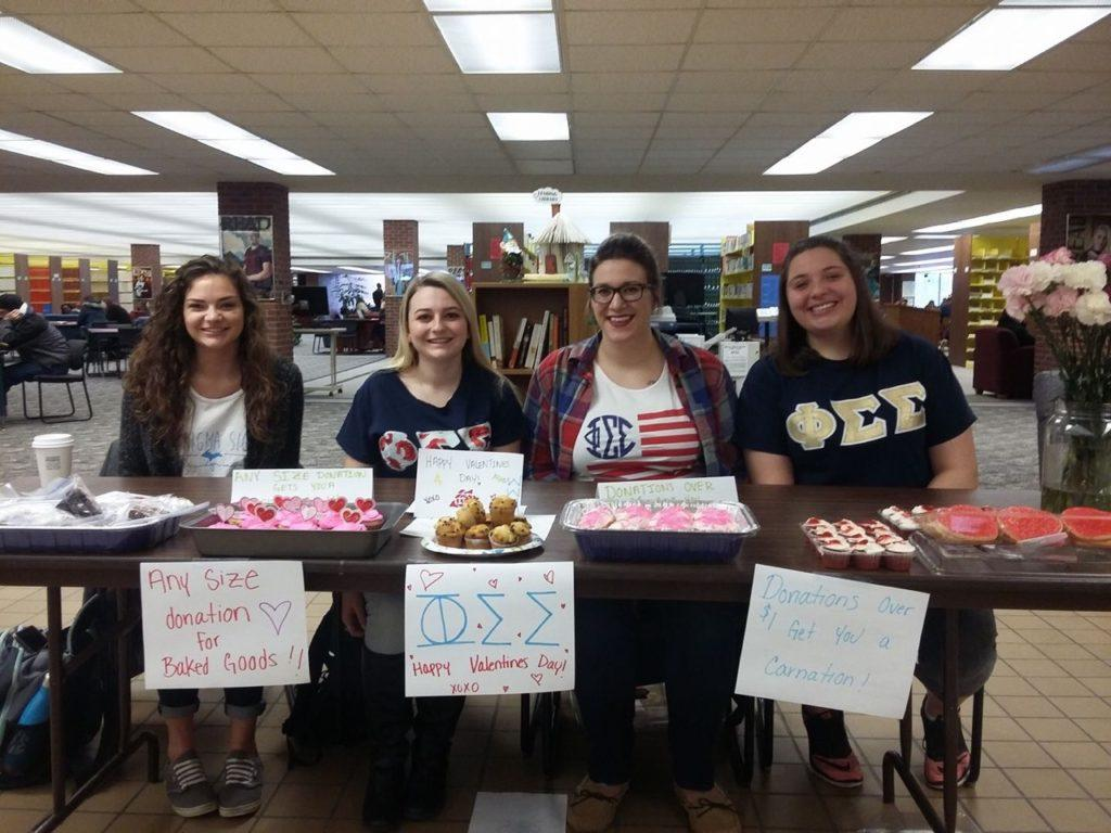 Photo courtesy of Lucas Lafave SWEET AS SUGAR—Phi Sigma Sigma members Amber Rewa (left), Jackie Menzel-Cranney, Norelle Lynch and Ariana Beukema host a bake sale fundraiser in the Lydia M. Olson Library.