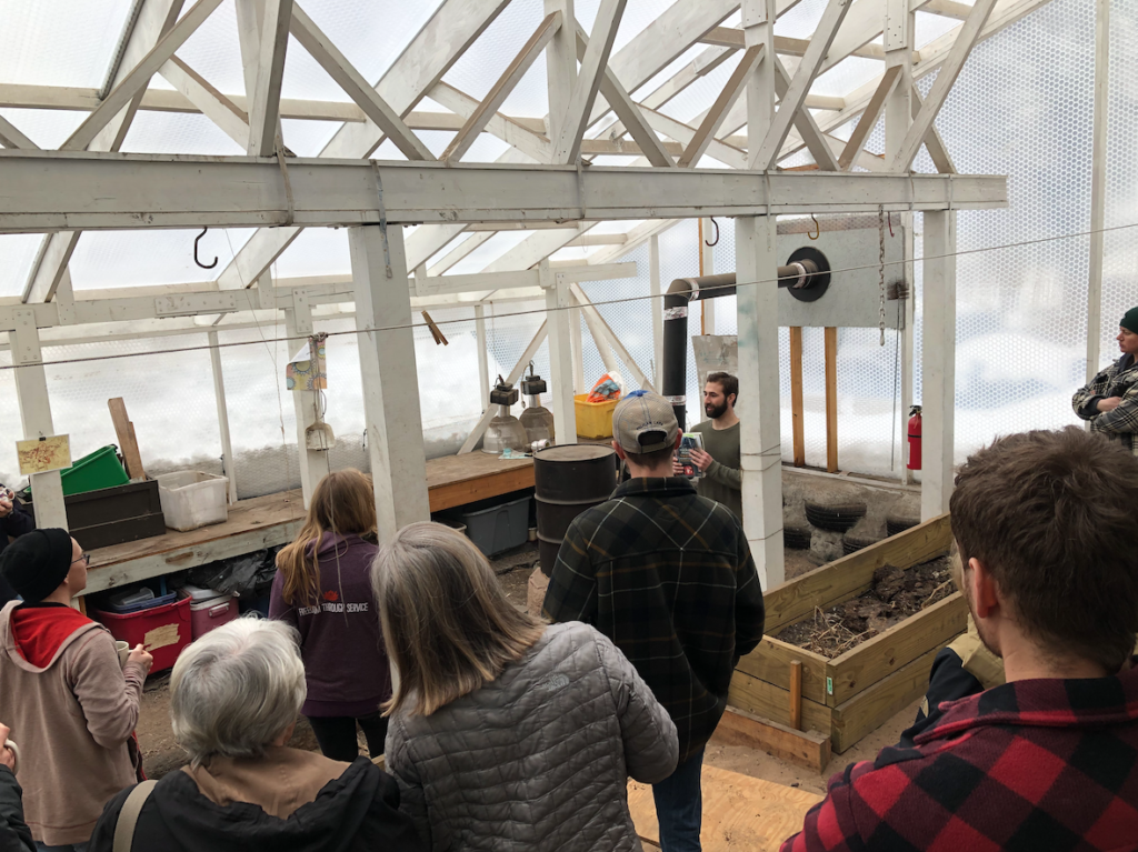 """Photo courtesy of Marquette Climbers Cooperative  DOWN AND DIRTY—Community members gather in the Marquette Climber's Cooperative greenhouse on Saturday, Jan. 25 to learn about sustainable gardening. Senior biology major Bryce DeMers, member of the co-op refers to the text, """"The Rocket Mass Heater Builder's Guide"""" when explaining the greenhouse dynamic. The rocket mass heater they use is a space heating system expanded from a type of efficient wood burning stove, the rocket stove."""
