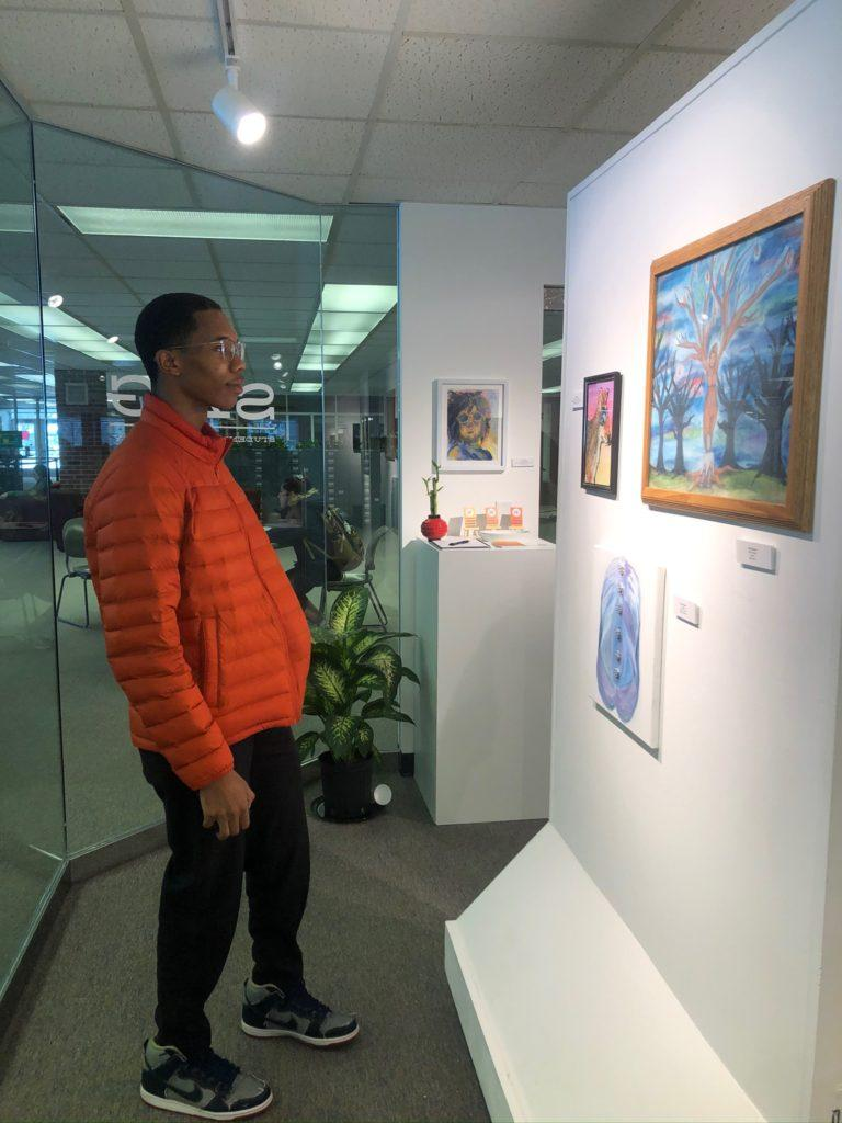 Maggie Duly/NW STOP AND STARE—Ali Davis, junior graphic design major, admires several paintings decorating the exhibit.