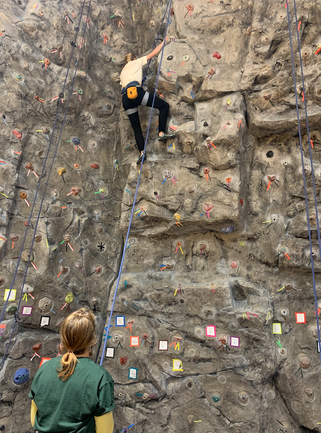 Ashley Beronja/NW ALMOST THERE—Junior environmental studies and sustainability major, Hailey Pampreen, follows routes outlined on the Outdoor Recreation Center rock wall during Women on the Wall event on Sunday, Feb. 9.