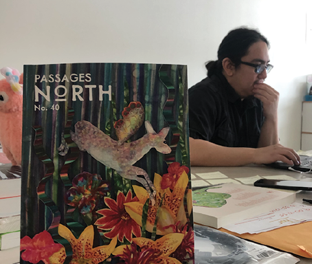 Maggie Duly/NW TO ACCEPT OR NOT—Graduate assistant T Guzman sifts through recent submissions to Passages North for next spring's edition. Passages North's 40th edition cover was designed by Associate English Professor Monica McFawn.