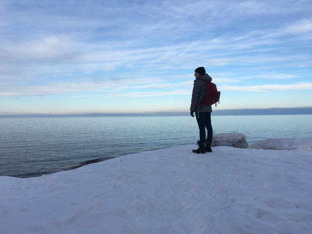 DON'T LOOK DOWN—At Little Presque Park, Freshman business finance major Anna Platz gazes over Lake Superior's vast surface, poised on a treacherous platform of ice at the shore's edge.