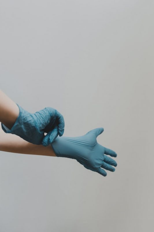 Hands putting on protective gloves