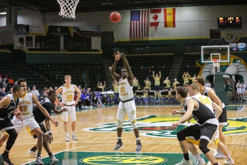 NMU student shoots basketball during game.