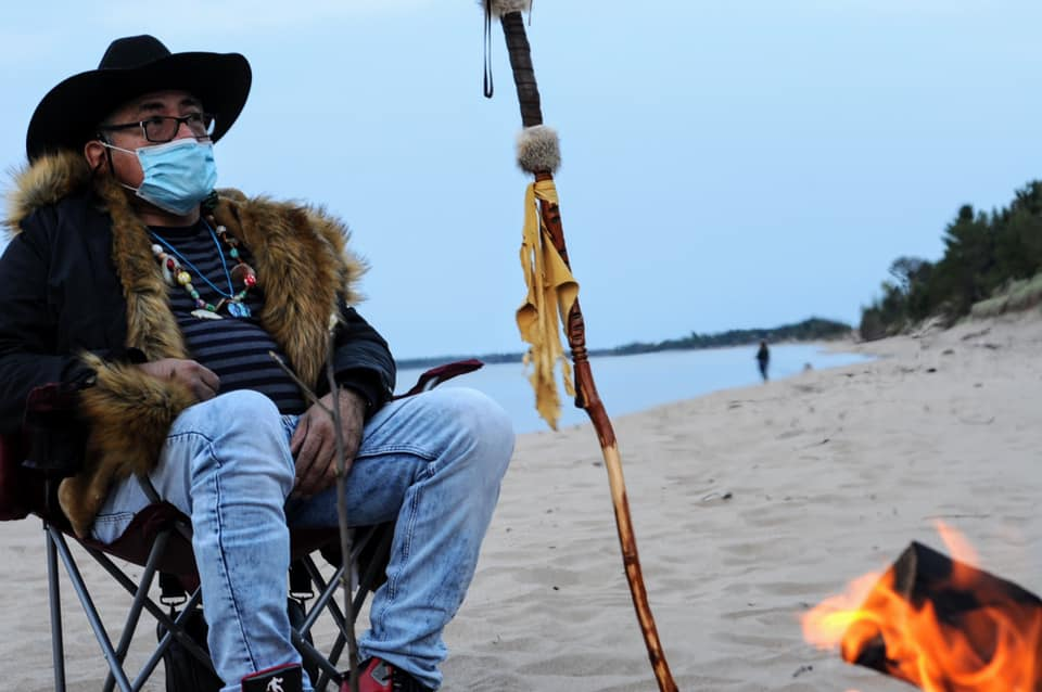 Picture of Joseph Calderon sitting on the beach listening to stories.