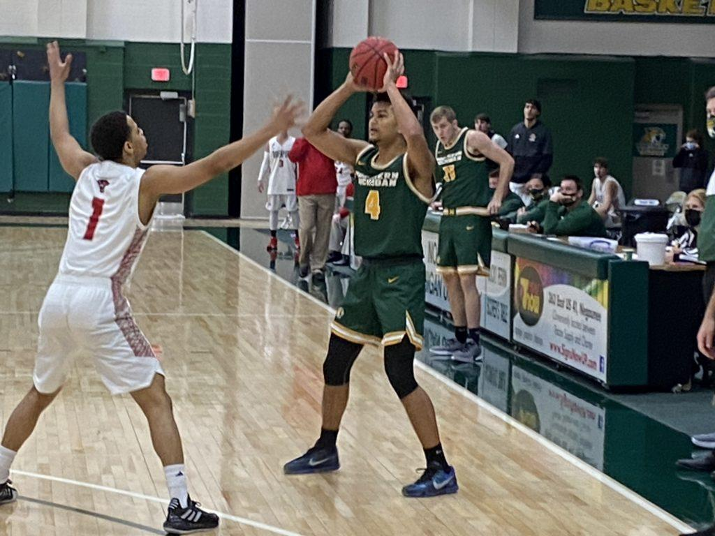 HOME SWEEP HOME—NMU junior guard Max Bjorklund looks to pass during the Wildcats 66-54 win over Davenport. Northern won both games in the home series. Travis Nelson/NW